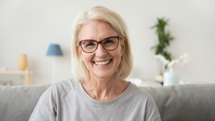 White lady with grey hair smiling at camera
