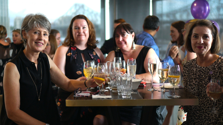 four women sitting at a table drinking at a cocktail party